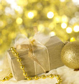Golden holiday arrangement with gift box — Stock Photo