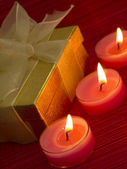 Burning candles with gift box — Stock Photo