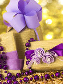 Golden gift boxes with beautiful purple decoration — Stock Photo