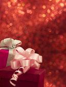 Coffrets cadeaux avec noeuds sur le fond rouge brillant — Photo