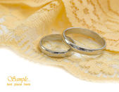 Golden wedding rings on the yellow textile background — Stock Photo