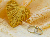 Yellow heart and wedding rings — Stock Photo