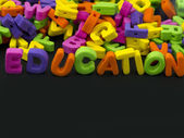 Education title written of rubber letters on the black background — Stock Photo