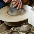 Stock Photo: Potter's wheel and hands of craftsmhold jug