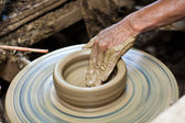 Potter's wheel and hands of craftsman hold a jug. — Stock Photo