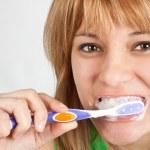 Beautiful blond girl brushing her teeth — Stock Photo