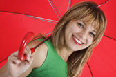 A portarit of a young woman with a red umbrella — Stock Photo