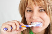 Beautiful blond girl brushing her teeth — Stock Photo