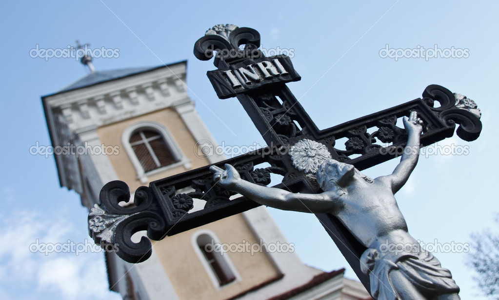 Closeup of a crucifixwith Christ with the tower of a Roman catholic church in the background — Stock Photo #11269283