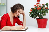 Young woman at home writing — Stock Photo