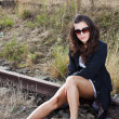 Brunette sitting on rail close - Stock Photo