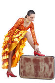 Flamenco dancer putting on red shoe on suitcase — Stock Photo