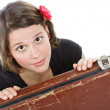Attractive young woman looking from behind a suitcase — Stock Photo