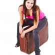 Beautiful young woman sitting on old suitcase — Stock Photo