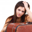 Beautiful young woman leaning on old suitcase — Stock Photo