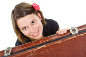 Beautiful young woman smiling from behind a suitcase — Stock Photo