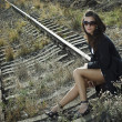 Brunette sitting on rail close — Stock Photo