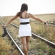 Picture of young woman with sandal in hand on the railway - Stock Photo