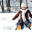 Young woman sitting in snow — Stock Photo