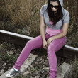 Sad young woman sitting on the railroad — Stock Photo #11641788