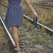 Young woman with shoes in her hand on the railway - Stock Photo