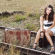 Young woman sitting on railroad — Stock Photo #11641804