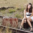 Stock Photo: Young woman sitting on railroad