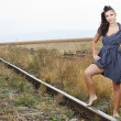 Stock Photo: Beautiful young woman on the railroad