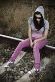 Sad young woman sitting on the railroad — Stock Photo