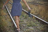 Young woman with shoes in her hand on the railway — Stock Photo