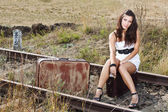 Young woman sitting on railroad — Stock Photo