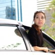 Young pretty Asian girl looking at back of car — Stok fotoğraf