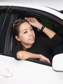 Young pretty Asian girl looking forward of car — Stock Photo