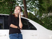 Young pretty Asian standing near car and calling by phone — Stock Photo