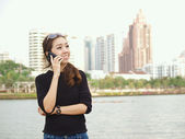 Pretty Asian calling by phone with building background — Stock Photo