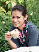 Asian woman holding a cup of tea or coffee and smiling — Stock Photo