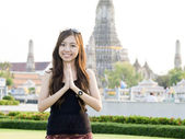 Attractive asian woman greeting with Temple of Dawn Wat Arun bac — Stock Photo