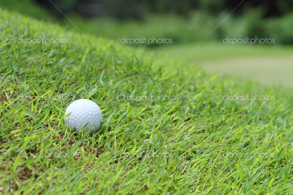 Golf ball on slope grass green — Stock Photo #12054044