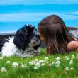 Stock Photo: Little girl and puppy kissing