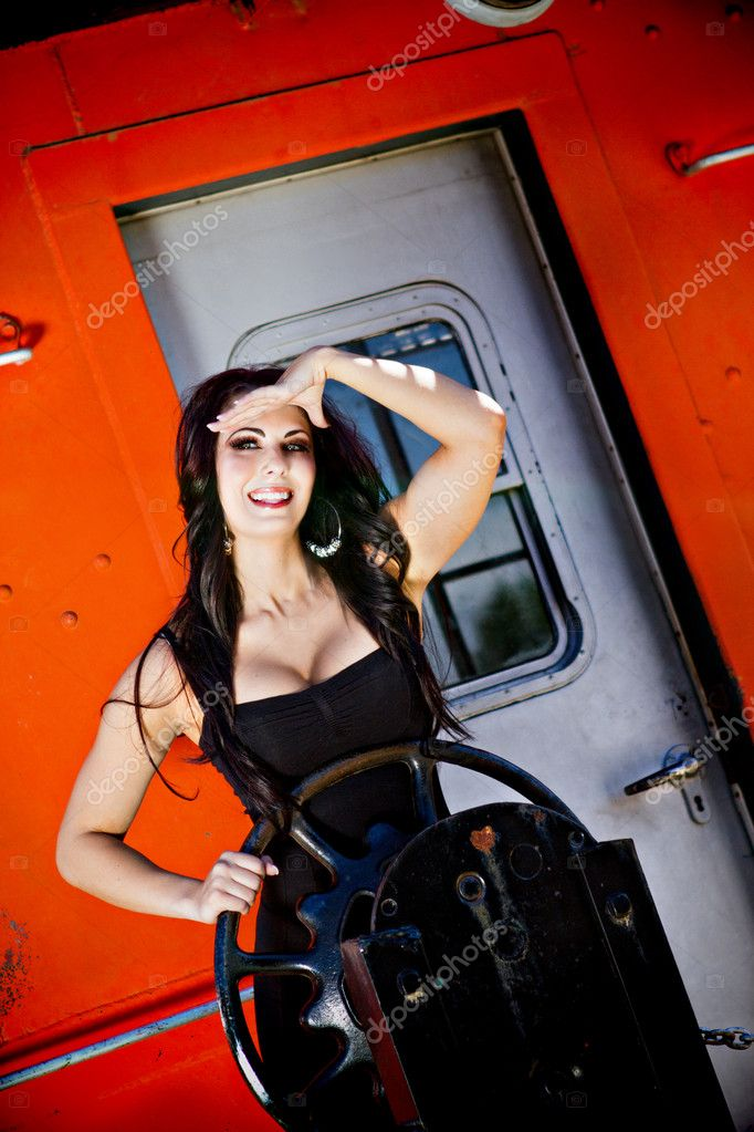 A gorgeous young woman is looking out from the back of a train while holding on to a wheel. — Stock Photo #11225779