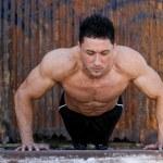 Young caucasian male in sportswear doing push ups — Stock Photo