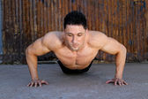 Young caucasian male in sportswear doing push ups — Stock Photo
