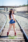 Beautiful cowgirl near the railroad — Stock Photo
