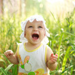 Screaming of baby lost in green meadow — Stock Photo