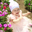 Upset little baby in flowers field — Stock Photo