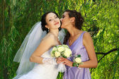 The young girl kisses the bride on a background of greens — Stock Photo