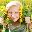 Royalty-Free Stock Photo: Young girl in the field playing with sunflowers