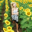 Happy young blonde girl running in the field of sunflowers — Stock Photo