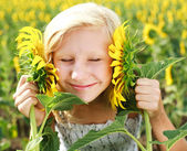 Young girl in the field playing with sunflowers — Stock Photo