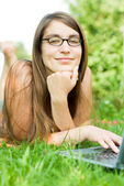 Girl outside on laptop — Stock Photo